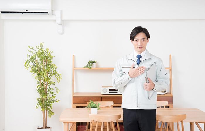 作業着姿の男性がこっちを見ている